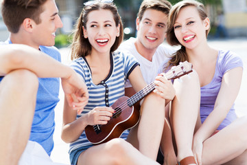 Young woman playing ukulele for friends