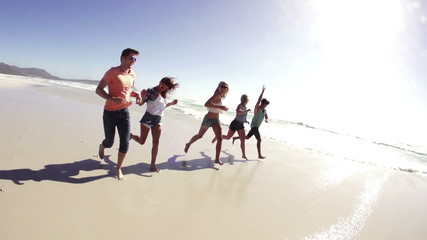 Friends running along the beach