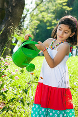 Pretty young girl watering flowers in the garden.