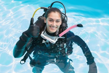 Smiling woman on scuba training in swimming pool showing thumbs