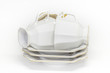 Three porcelain coffee cups lie on a pile of saucers