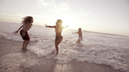 Friends splashing water at the beach