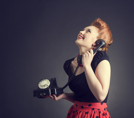 Cheerful woman talking on land line phone.