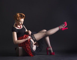 woman in retro style flirtatiously straightens stockings