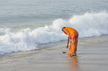 indian woman with colorful sari on sea beach