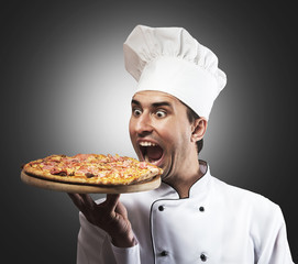 Funny portrait of a chef with opened mouth looking at pizza