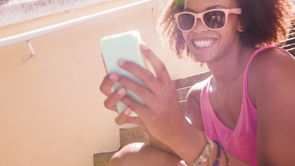 Afro haired girl texting on smartphone