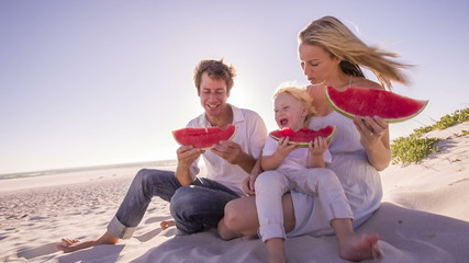 Family at beach eating watermelon