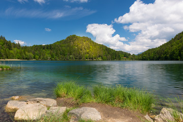 sunny spot on mountain at lake alatsee with rocks and grass