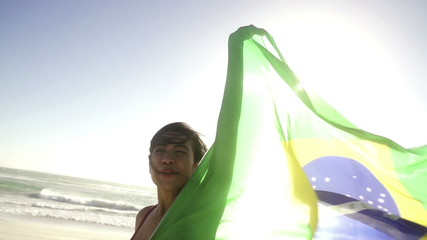 Woman waving brazilian flag at the beach in slow motion
