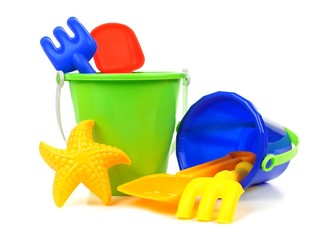 Toy sand pails and shovels over a white background