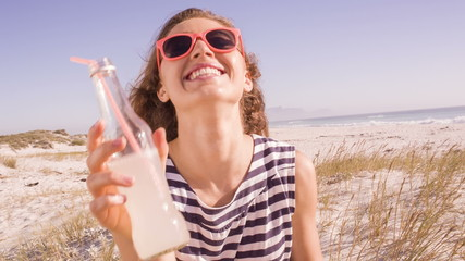 Teenager toasting to camera with lemonade at the beach