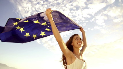 European Woman holding EU flag against sky waving