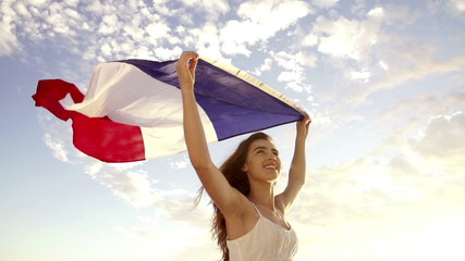 French woman holding up the Tricolor Flag waving