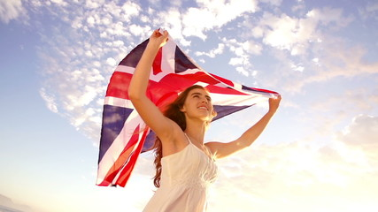 British woman holding Union Jack flag waving in slow motion
