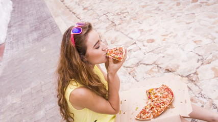 Young woman eating a pizza sitting in the street