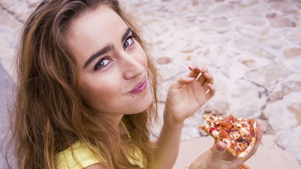 Young woman biting into slice of pizza sitting in the street
