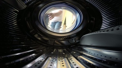 Man removes his shirt and puts it in the washing machine