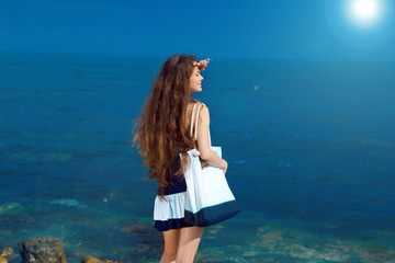 Happy Young woman with long wavy hair posing over blue sea sky.