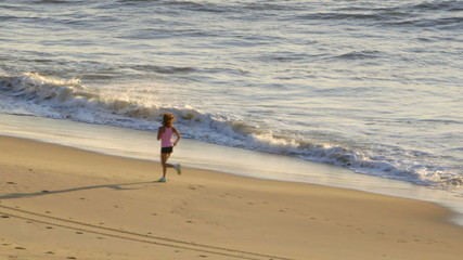 Woman jogs on beach at sunrise