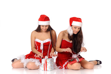 women in Christmas costumes open presents