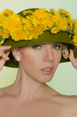 Young woman in helmet with a wreath of dandelions