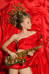 Woman with golden saxophone lying on red silk