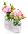Beautiful bouquet of bright flowers in jars isolated on white