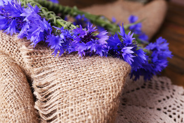 Fresh cornflower wreath on sackcloth background