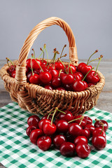 Sweet cherries in wicker basket on wooden table