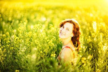 Woman enjoying sunlight in canola field