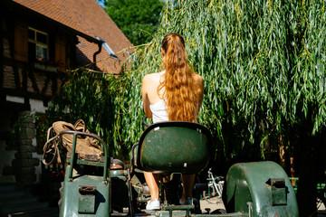 Jungbäuerin auf altem Traktor