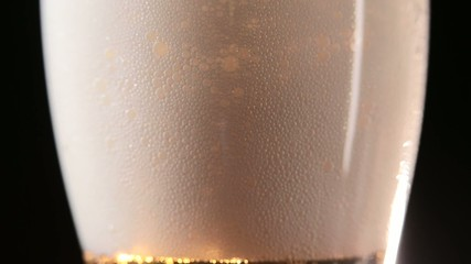 Beer mug with froth over black background