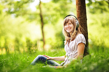 Young woman sitting on grass listening music with big headphones