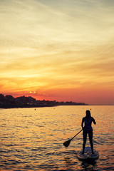 Silhouette of standup paddle boarding performance by girl