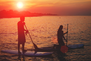 Couple doing standup paddle boarding at the orange sunset