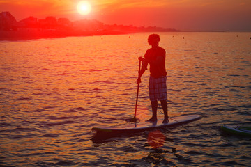 Silhouette of standup paddle boarding performed by man