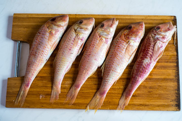 Five raw red fishes on wooden cutting board