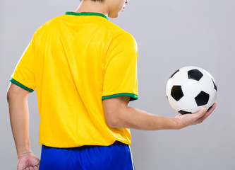 Rear view of football player hold with soccer ball