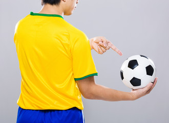 Back view of sportman finger point to soccer ball