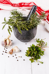 Fresh herbs in mortar over white wooden background