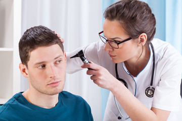 Young doctor examining patient's ears