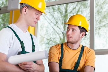 Two men in overalls and hardhat during work