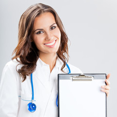 Female doctor showing blank clipboard, on grey