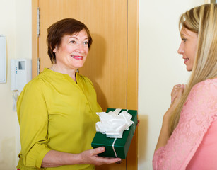 senior neighbor presenting gift to young girl
