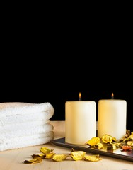 Spa massage with towel stacked, perfumed leaves and candles