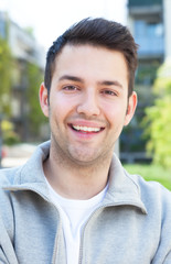 Hispanic guy in a grey jacket with crossed arms outside