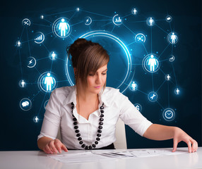 Businesswoman sitting at desk with social network icons