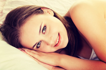 Smiling young woman in bed