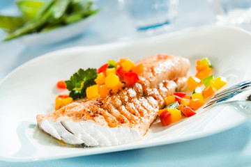 Grilled fish fillet with a colorful fresh salad